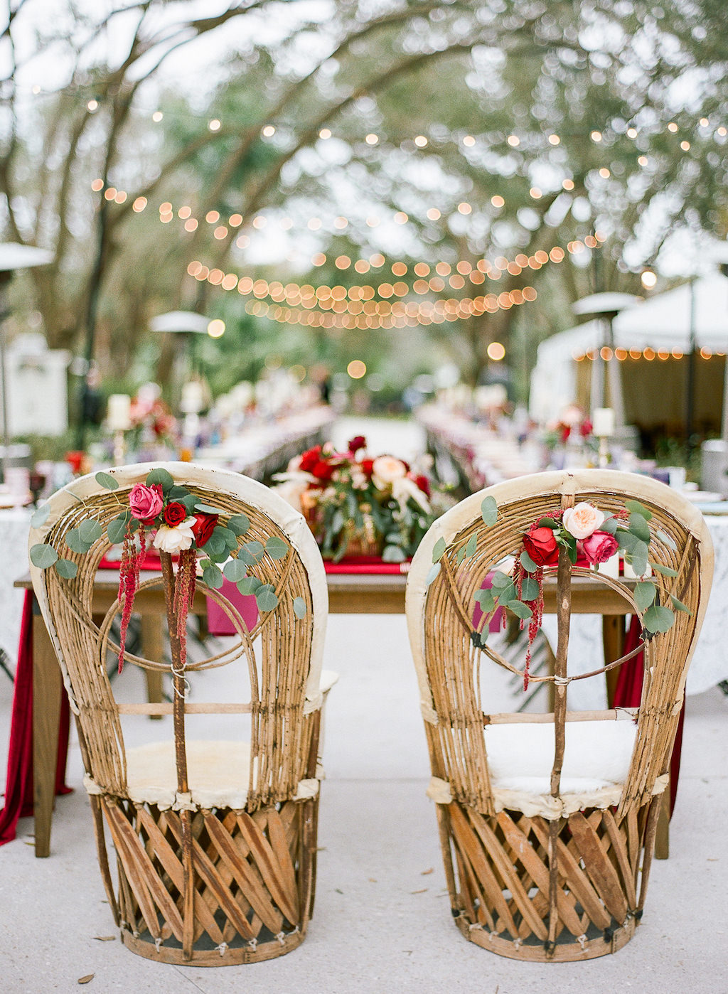 Boho Chic Vintage Inspired Outdoor Lakeland Florida Wedding Reception Decor, Wicker Chairs with Red, Pink, White and Greenery Florals on Wicker Chairs for Sweetheart Table