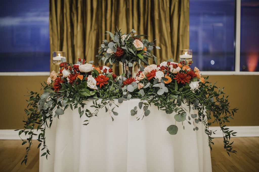 Romantic, Florida Ballroom Reception Wedding Decor, Sweetheart Table with White Linen, Greenery, Red, Orange and Blush Floral Garland and Floral Bouquet in Tall Glass Vase Centerpiece