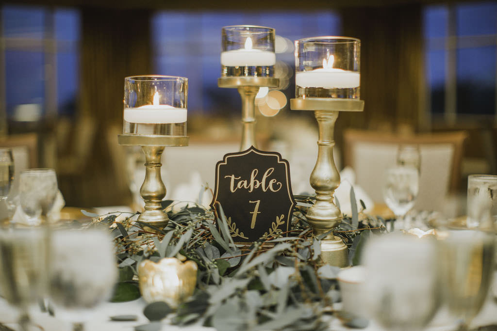 Romantic, Wedding Florida Ballroom Reception Decor, Gold Candlesticks with Floating Candles, Black and Gold Table Number and Greenery Flowers