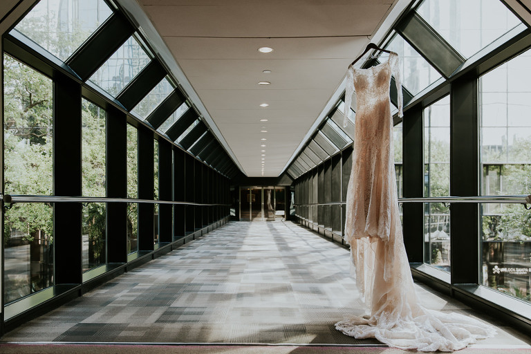 Illusion and Lace Off White Long Sleeve High Scoop Neckline Wedding Dress Hanging in Glass Window Hotel Tunnel Hallway | Tampa Bay Wedding Photographer Brandi Image Photography | Downtown Tampa Hotel Wedding Venue Hilton Tampa Downtown