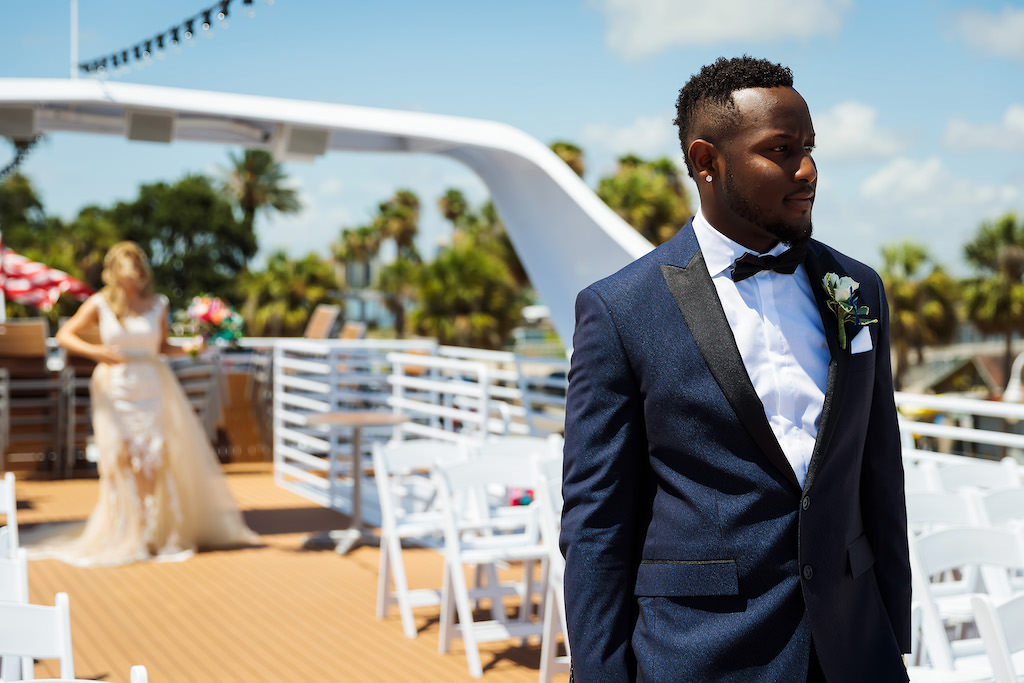 Florida Bride and Groom First Look Wedding Portrait on Deck of Yacht, Groom in Navy Blue Tuxedo with White Floral Boutonniere | Tampa Bay Waterfront Wedding Venue Yacht Starship IV