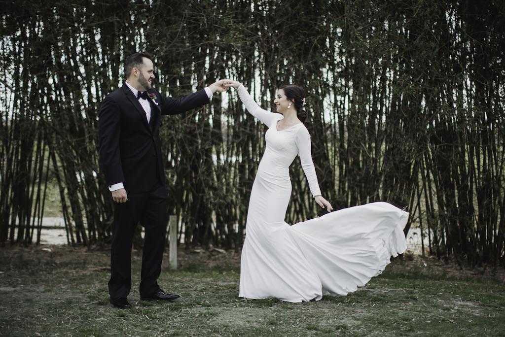 Outdoor Florida Bride and Groom First Look Wedding Portrait, Bride in Long Sleeve V-Neckline Crepe and Lace Wedding Dress, Groom in Black Tuxedo