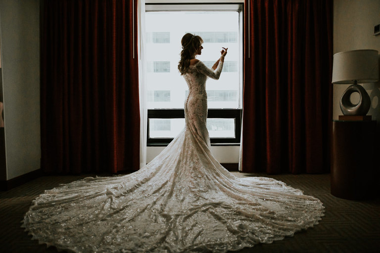 Bride Getting Ready Wedding Portrait, Bride in Lace and Illusion Long Sleeve and Elegant Train Wedding Dress | Tampa Bay Wedding Photographer Brandi Image Photography | Downtown Tampa Wedding Venue Hilton Tampa Downtown