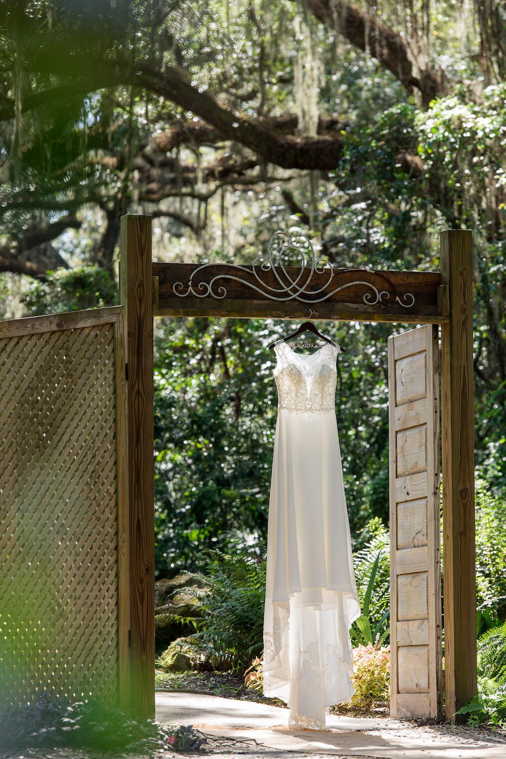 Lace and Chiffon A-Line High Neckline Wedding Dress Hanging on Garden Door Entrance | Tampa Wedding Venue Kathleen's Garden