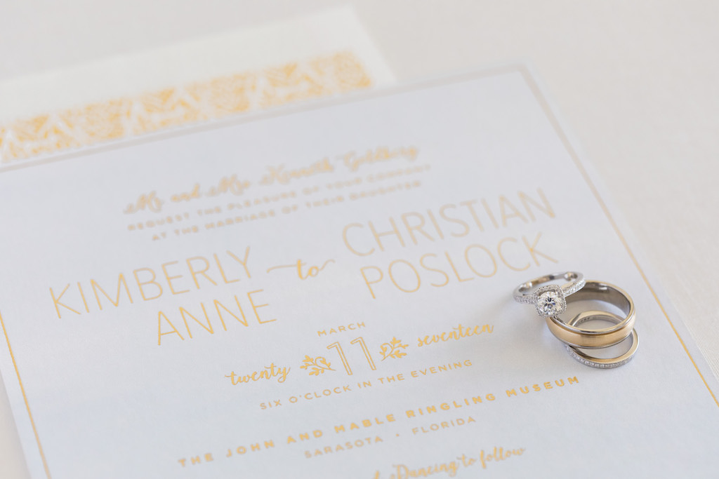 Modern Gold Foil and White Wedding Invitation, Round Diamond Halo Engagement Ring, Yellow Gold Groom Wedding Ring and Yellow Gold and Diamond Bride Wedding Ring