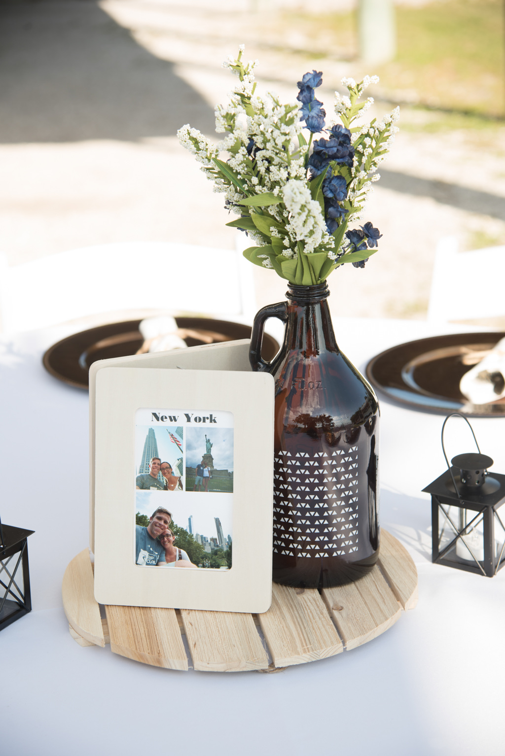 Rustic Wedding Reception Decor, Round Wooden Tray, Photo of Couple on Wooden Frame, Beer Growler Glass Bottle with White, Blue and Greenery Floral Centerpiece | Tampa Bay Florist Cotton and Magnolia