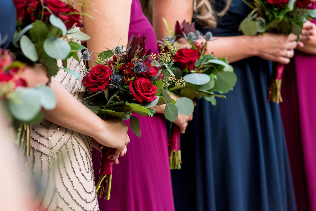 Florida Bridesmaids in Mismatched Dark Pink, Purple, Blue and Nude Rhinestone Dresses with Wild Organic Red, Lilac and Greenery Floral Bouquets with Burgundy Sashes