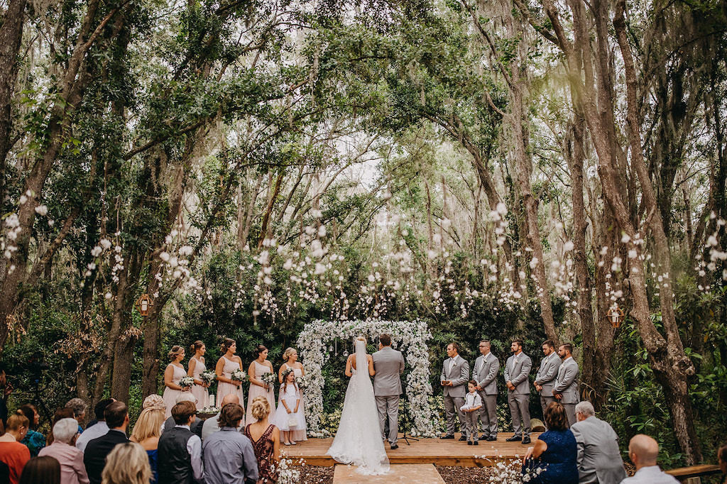 Elegant Outdoor Rustic Wedding Ceremony Decor, Bride and Groom Wedding Portrait, White and Greenery Floral Arch with Hanging Glass Bulbs | Lakeland Rustic Wedding Venue The Prairie Glenn Barn at Gable Oaks Ranch