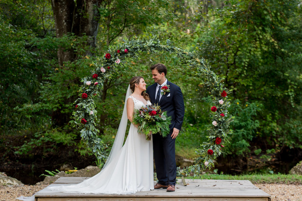 Florida Bride and Groom Wedding Portrait, Bride with Wild Organic Greenery Red, Burgundy, Lilac Floral Bouquet, Round Circular Arch Covered in Greenery, Dark Red, Burgundy, Blush Pink Roses Backdrop | Rustic Wedding Venue Kathleen's Garden