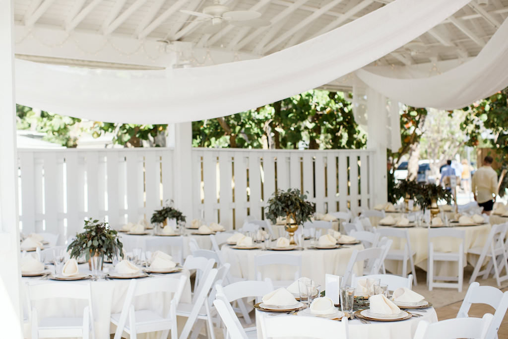 Tropical Inspired Wedding Reception Decor, Round Tables with White Tablecloths, Low Gold Vases with Greenery Centerpieces | Sarasota Beachfront Wedding Venue Sandbar Waterfront Restaurant