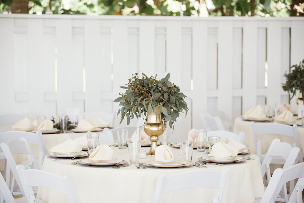 Tropical Inspired Wedding Reception Decor, Round Tables with Ivory Tablecloths, Low Gold Vases with Greenery Centerpieces, White Folding Chairs