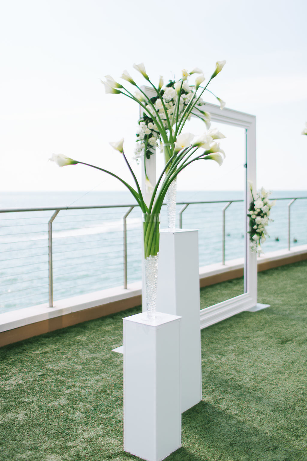 Modern Elegant Waterfront And Lawn Wedding Ceremony Decor White Frame With Greenery And White Floral Arrangements Tall White Pedestals With White Tulips Tampa Bay Wedding Photographer Kera Photography Clearwater Beach