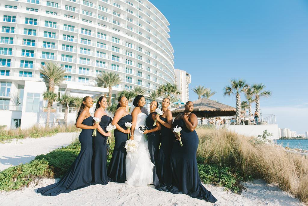 Beachfront Bride and Bridesmaids Wedding Portrait, Bridesmaids in Matching Strapless Navy Blue Long Dresses | Tampa Bay Wedding Photographer Kera Photography | Clearwater Beach Wedding Venue Opal Sands Resort