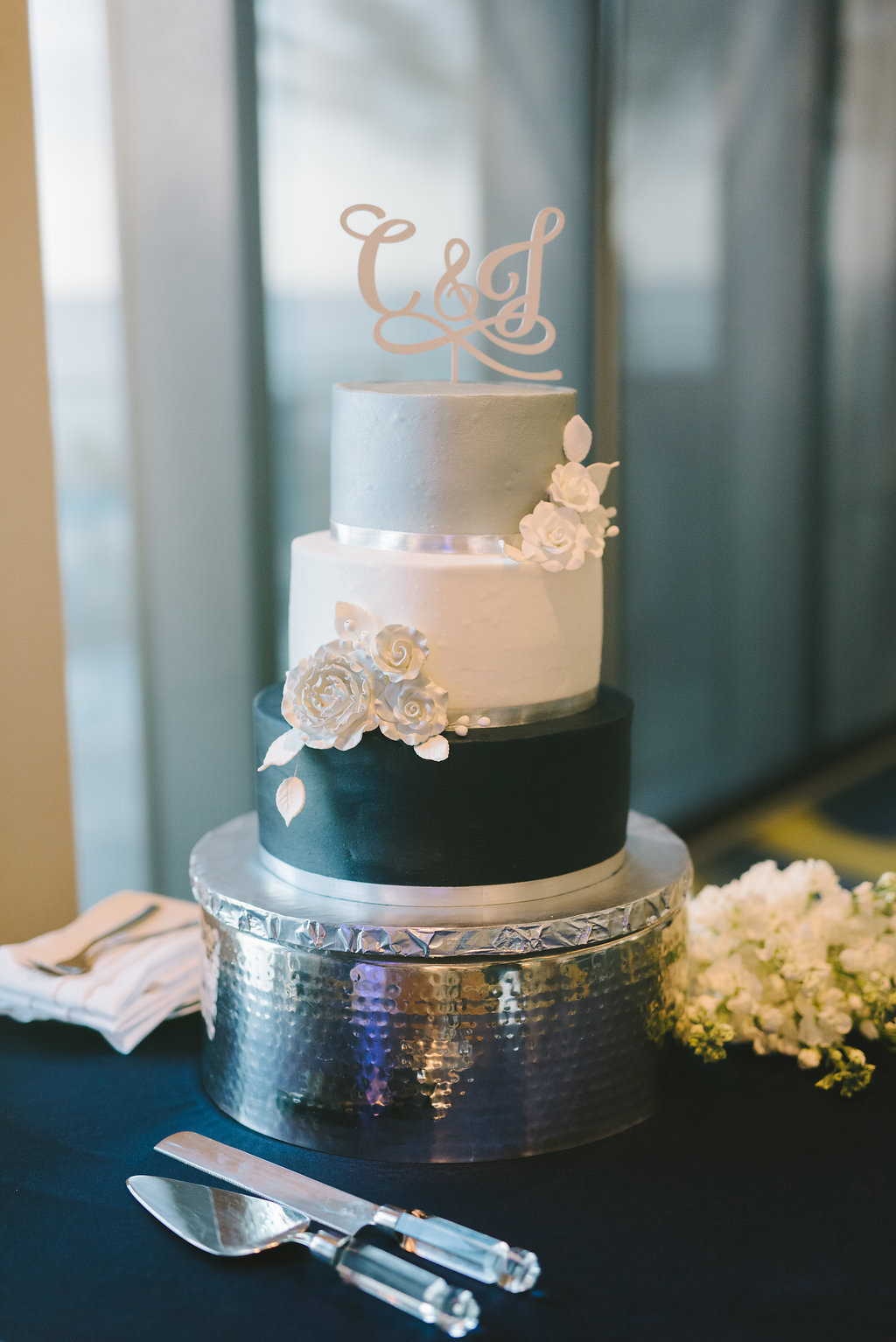 Three Tier White Silver And Navy Blue Wedding Cake With White Sugar