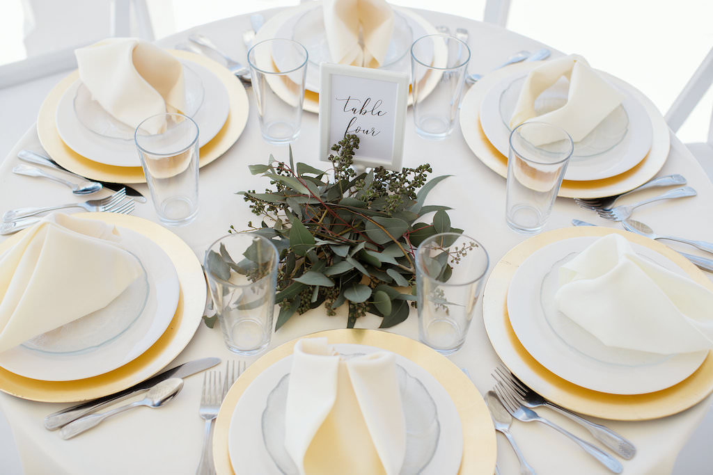 Tropical Inspired Wedding Reception Decor, Round Tables with Ivory Tablecloths, Gold Chargers, Low Gold Vases with Greenery Centerpieces, White Folding Chairs