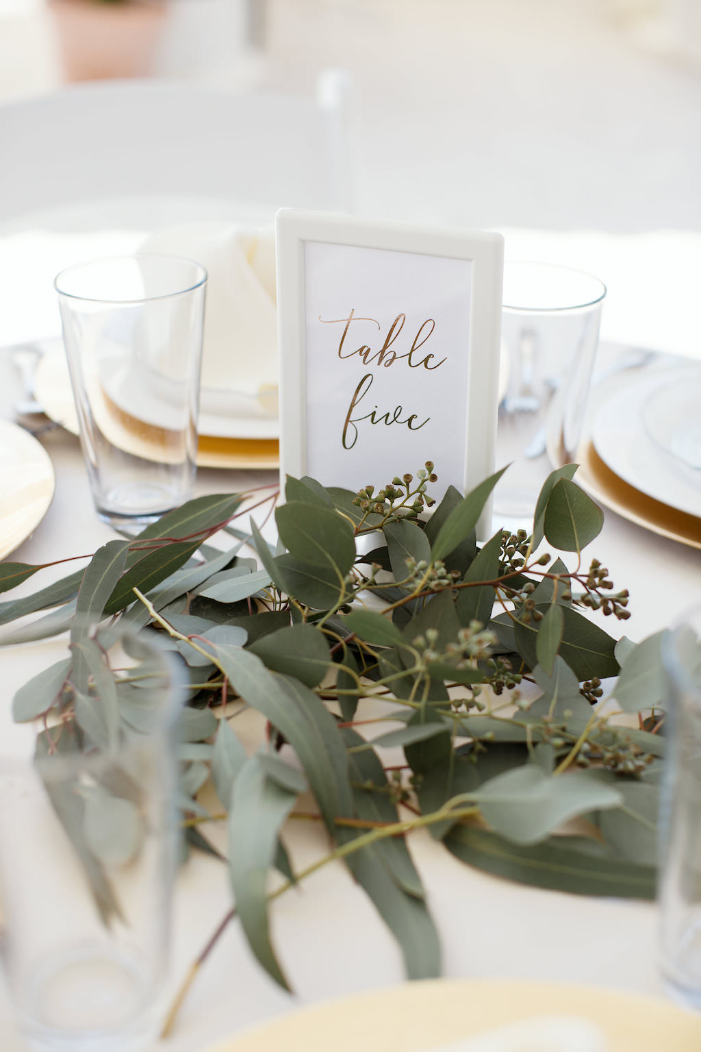 Tropical Inspired Wedding Reception Decor, Round Tables with Ivory Tablecloths, Gold Chargers, Greenery Centerpiece, White Folding Chairs, Table Number in White Frame
