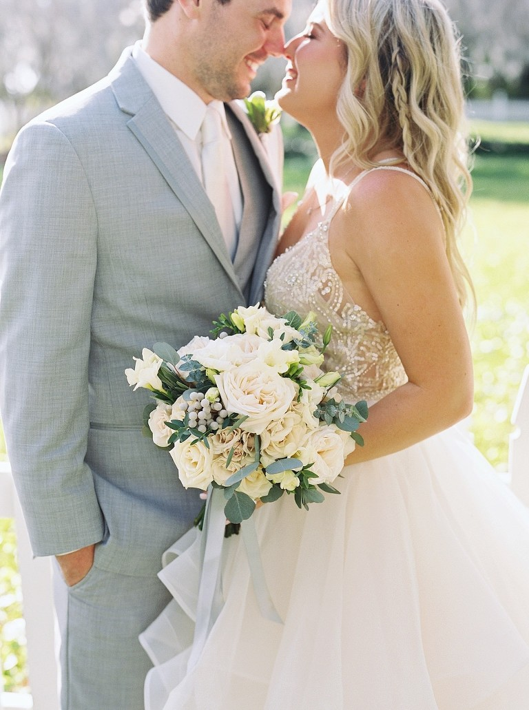 Florida Bride and Groom Outdoor Wedding Portrait, Bride in Nude Rhinestone Embellished Spaghetti Strap Bodice and Ivory Tulle Skirt Ballgown Watters Wedding Dress with Ivory Garden Roses and Silver Dollar Eucalyptus Greenery Floral Bouquet, Groom in Grey Suit with Blush Pink Tie | Florida Wedding Venue Palmetto Riverside Bed and Breakfast | Tampa Bay Wedding Florist Cotton & Magnolia