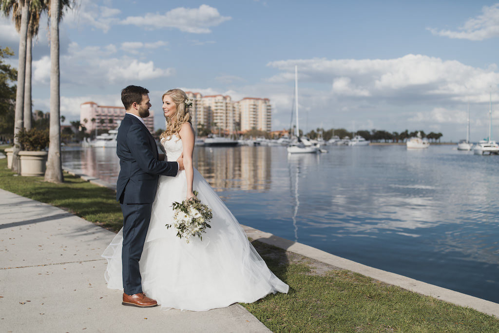 Outdoor Downtown St. Pete Waterfront Florida Bride and Groom Wedding Portrait, Bride in Strapless Hayley Paige Chantelle Gown, Ivory Tulle Skirt Ball Gown with Lace Corset Bodice, White and Greenery Floral Bouquet, Groom in Navy Blue Suit | Tampa Bay Wedding Hair and Makeup Artist Michele Renee the Studio