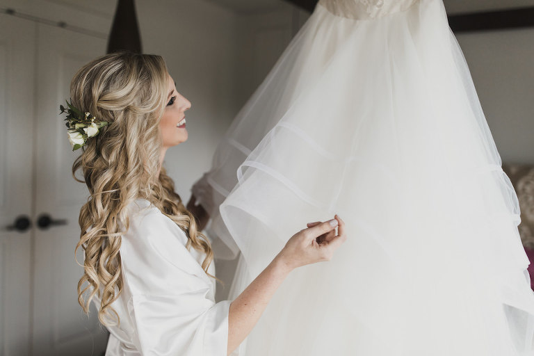 Florida Bride Getting Ready Wedding Portrait, Bride in White Silk Robe with Boho Chic Hair, Curls and Real White and Greenery Floral Headpiece Looking at Wedding Dress | Tampa Bay Wedding Hair and Makeup Artist Michele Renee the Studio