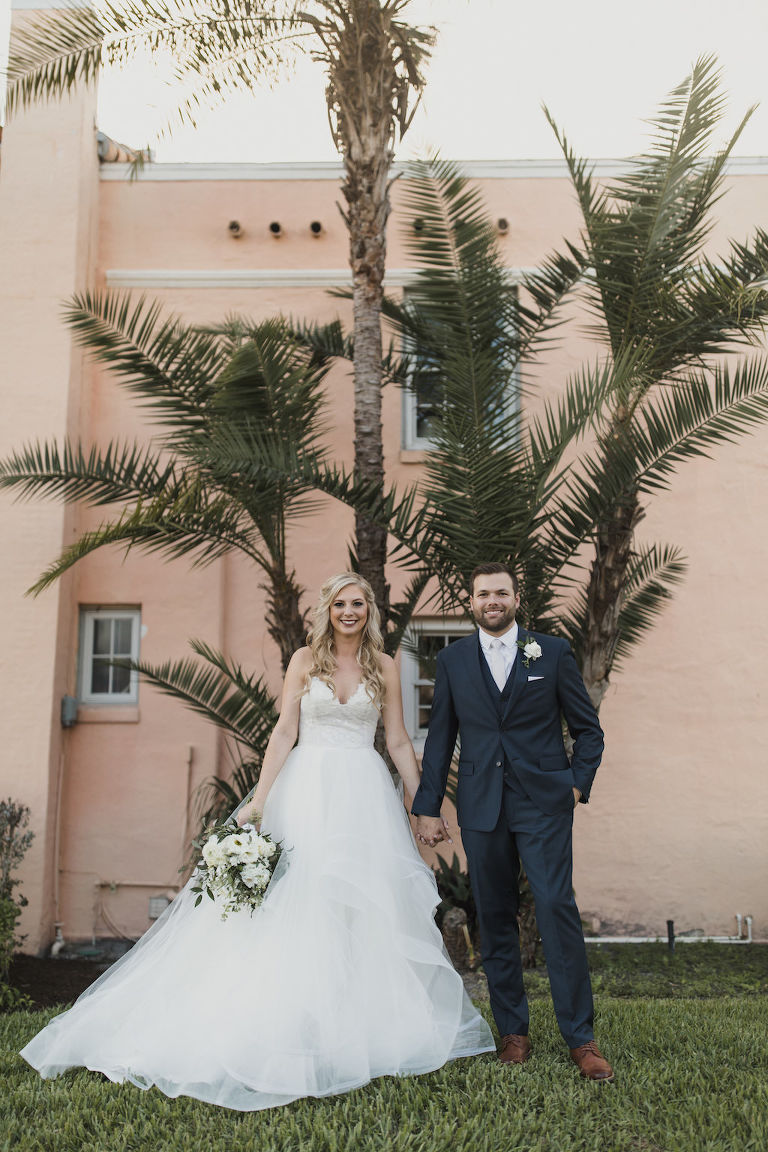 Outdoor Florida Bride and Groom Wedding Portrait, Bride in Strapless Hayley Paige Chantelle Gown, Ivory Tulle Skirt Ball Gown with Lace Corset Bodice, White and Greenery Floral Bouquet, Groom in Navy Blue Suit | Tampa Bay Wedding Hair and Makeup Artist Michele Renee the Studio