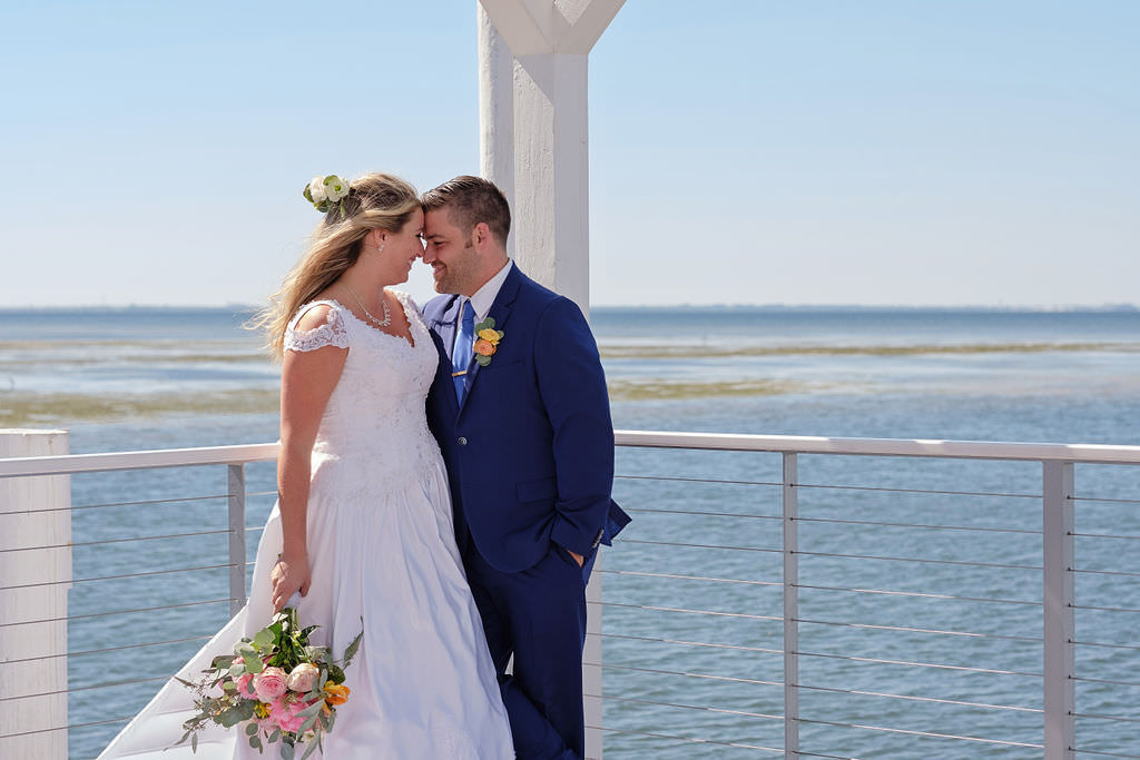 Waterfront Private Dock Bride and Groom Wedding Portrait, Bride in White Sweetheart Neckline with Cap Sleeves Ballgown Wedding Dress with Bright Pink, Orange, Ivory and Greenery Floral Bouquet, Groom in Blue Suit and Yellow and Orange Boutonniere | Island Inspired Wedding Venue The Godfrey Hotel and Cabanas Tampa | Tampa Bay Wedding Photographer Marc Edwards Photographs