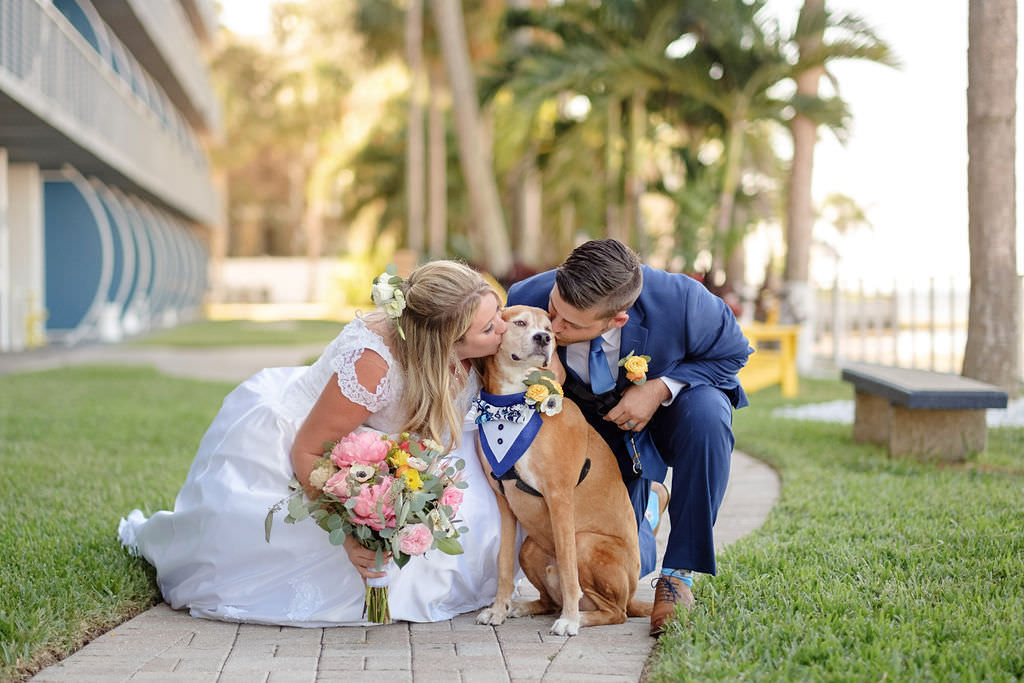 Florida Outdoor Bride and Groom Wedding Portrait, Bride in White Satin and Lace Cap Sleeve Ballgown Wedding Dress with Bright Pink, Yellow, White Anemone and Greenery Floral Bouquet, Groom in Blue Suit with Yellow and Orange Boutonniere, Dog in Blue Tuxedo | Waterfront Island Inspired The Godfrey Hotel and Cabanas Tampa | Tampa Bay Wedding Photographer Marc Edwards Photographs | FairyTail Pet Care
