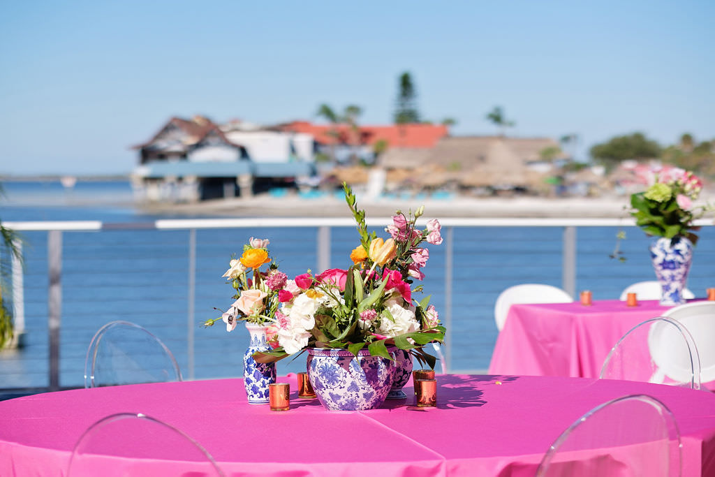 Citrus Inspired Waterfront Wedding Reception Decor, Round Table with Bright Pink Tablecloth, Clear Acrylic Ghost Chairs, Blue and White Vases with Ivory, Yellow, Pink and Greenery Floral Centerpiece | Island Inspired Wedding Venue The Godfrey Hotel and Cabanas | Tampa Bay Wedding Photographer Marc Edwards Photographs | Kate Ryan Event Rentals