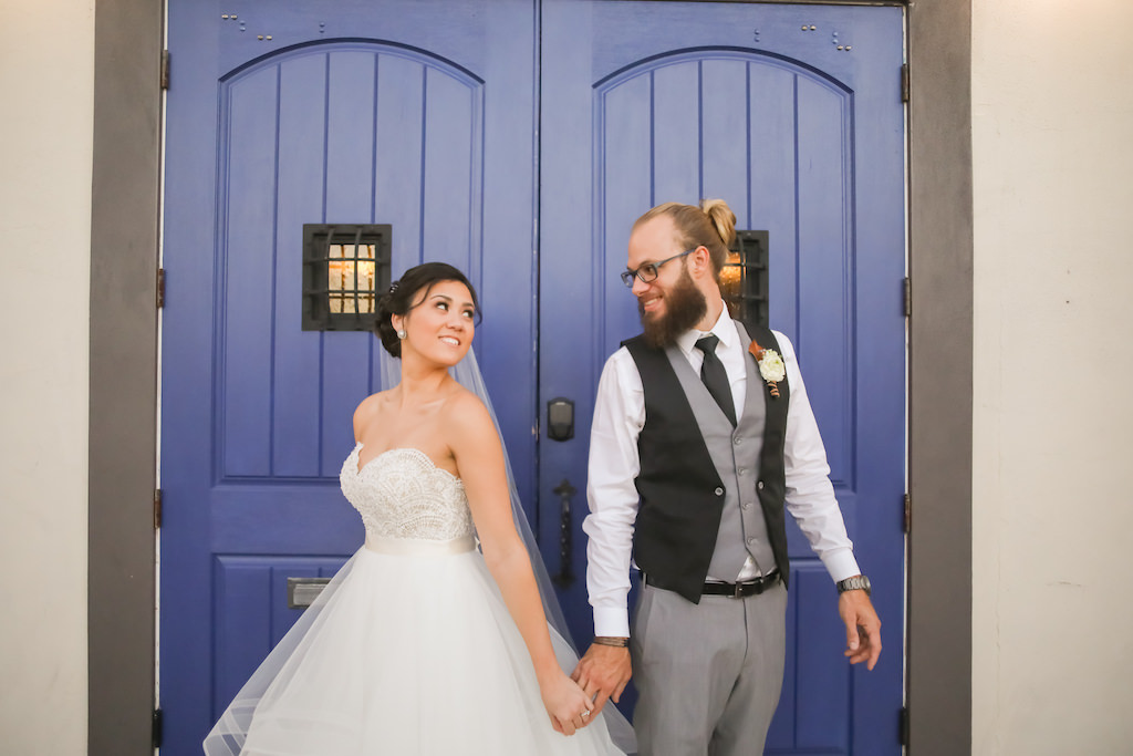 Florida Bride and Groom Wedding Portrait in Front of Blue Doors, Bride in Strapless Sweetheart Lace and Tulle Skirt with Satin Ribbon Ballgown Wedding Dress, Groom in Black and Grey Vest, Grey Dress Pants   Tampa Bay Wedding Photographer Lifelong Photography Studios