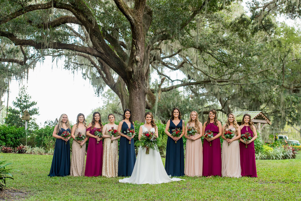 Florida Bride and Bridesmaids Outdoor Garden Wedding Portrait, Bridesmaids in Mismatched Navy Blue, Champagne, Magenta, and Nude Long Dresses with Organic Wild Garden Inspired Floral Bouquets | Rustic Wedding Venue Kathleen's Garden