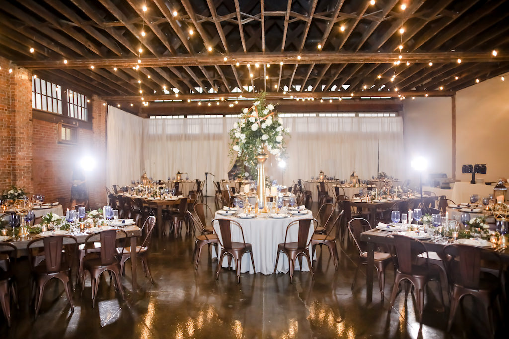 Industrial Inspired Wedding Reception Decor, Round and Long Feasting Tables, Bronze Metal Chairs, Tall Gold Vase with White and Greenery Floral Centerpiece   Tampa Bay Wedding Photographer Lifelong Photography Studios   Wedding Rentals A Chair Affair   Tampa Unique Industrial Wedding Venue CAVU
