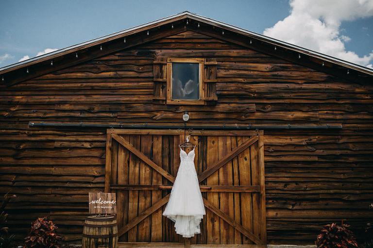 Rustic Inspired Wedding, Spaghetti Strap Lace A Line Wedding Dress Hanging Outside Barn | Lakeland Rustic Barn Wedding Venue The Prairie Glenn Barn at Gable Oaks Ranch