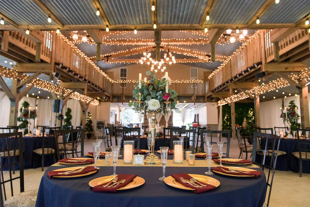 Rustic Wedding Reception Decor, Round Tables with Navy Blue Tablecloths, Gold Chargers and Burgundy Linens, Tall Silver Candlestick with Greenery, Ivory and Red Floral Bouquet Centerpiece, Gold Table Runner, Bistro Hanging Lights | Rustic Tampa Bay Wedding Venue Kathleen's Garden