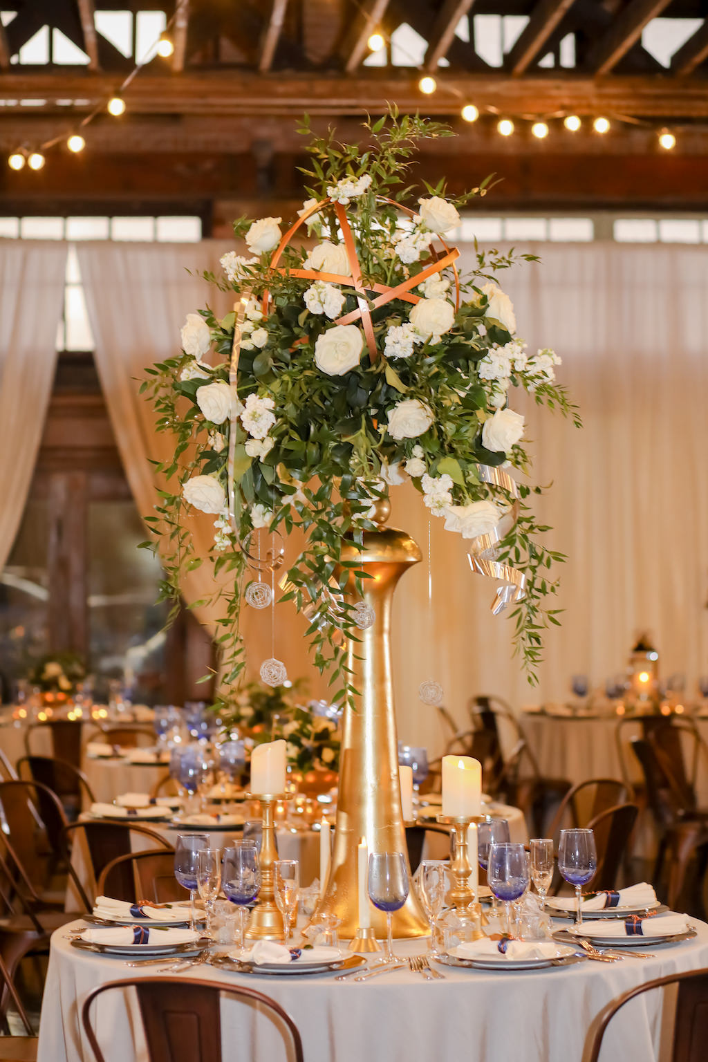 Industrial Inspired Wedding Reception Decor, Tall Gold Metal Vase with White and Greenery Florals in Geometric Circular Sphere with Hanging Crystals, Round Table with White Tablecloth, Blue Drinking Glasses, Bronze Metal Chairs   Tampa Bay Wedding Photographer Lifelong Photography Studios