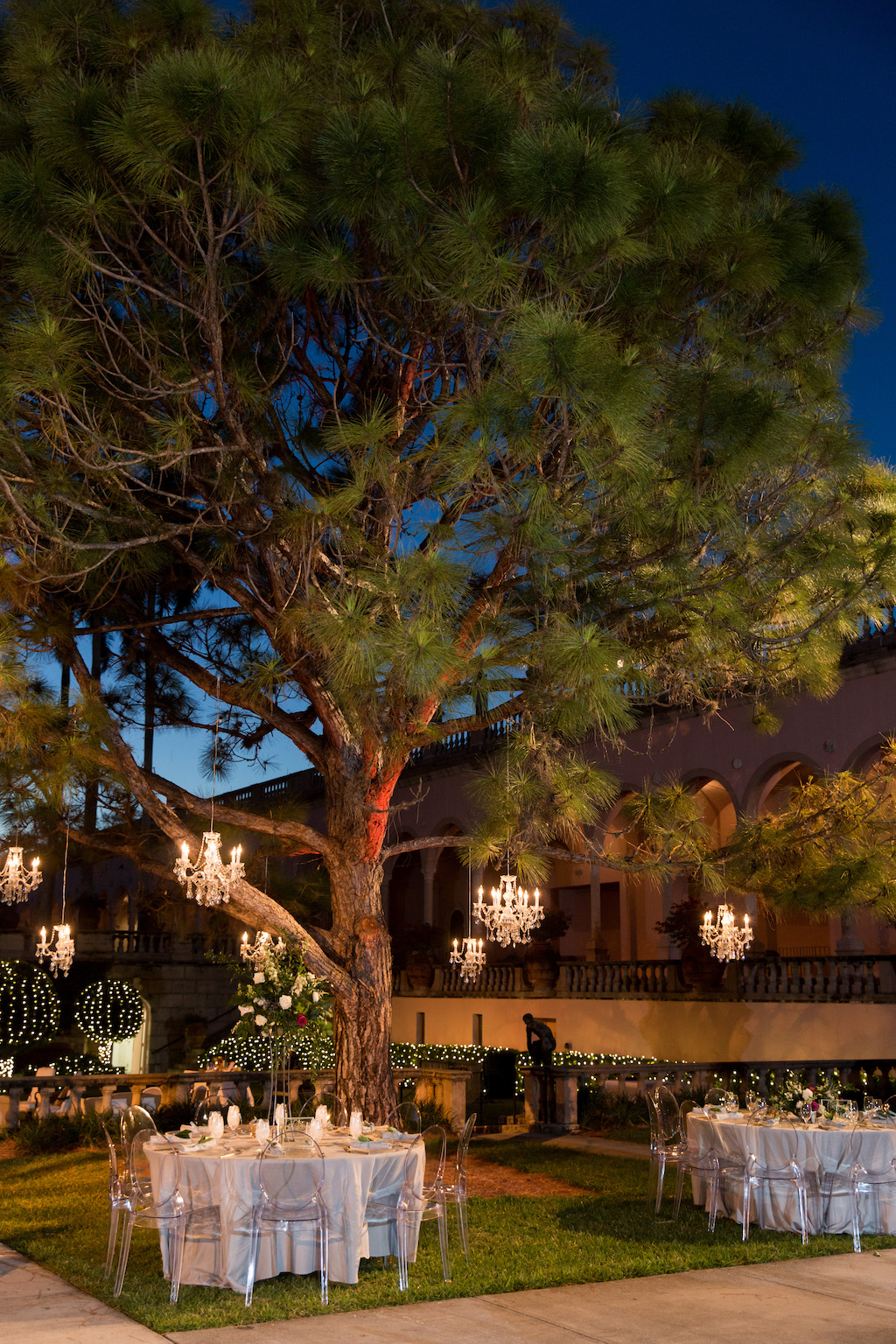 Nighttime Outdoor Garden Courtyard Wedding Reception Decor, Round Tables, Ghost Chairs, Crystal Chandeliers Hanging From Tree | Sarasota Wedding Venue Ringling Museum | Tampa Bay Wedding Planner NK Weddings