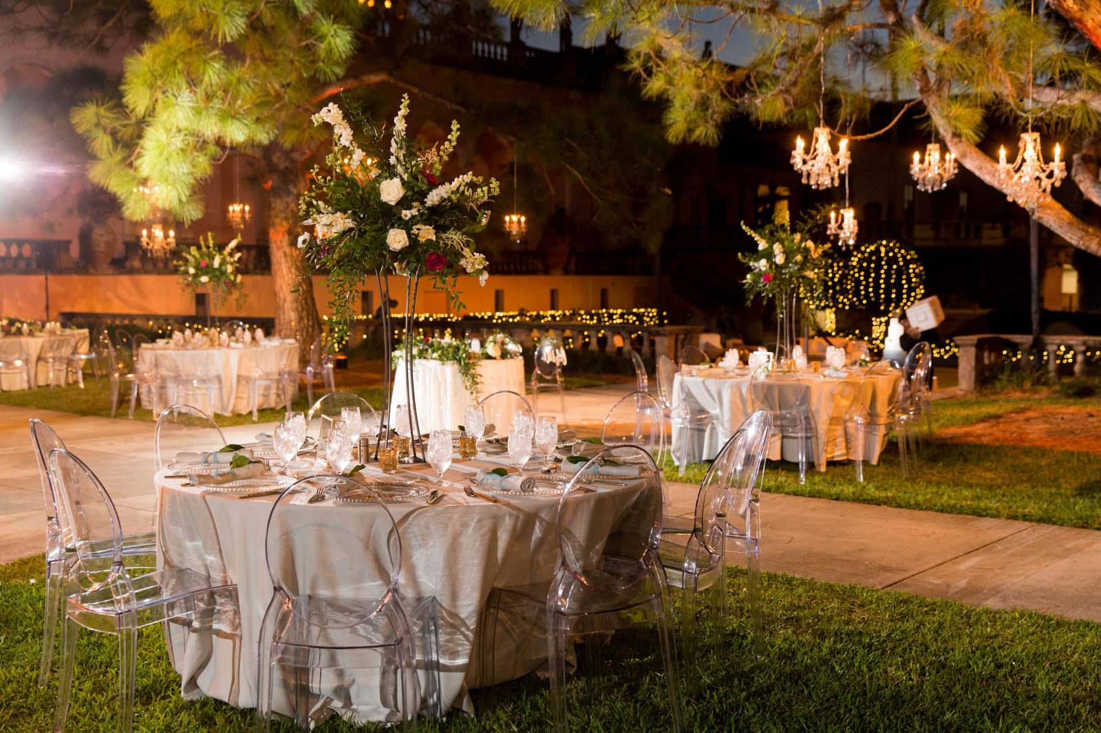Nighttime Outdoor Garden Courtyard Wedding Reception Decor, Round Tables with Ivory Tablecloths, Ghost Chairs, Tall Greenery, White, Ivory, Red Floral Centerpiece, Crystal Chandeliers Hanging From Tree   Sarasota Wedding Venue Ringling Museum   Tampa Bay Wedding Planner NK Weddings