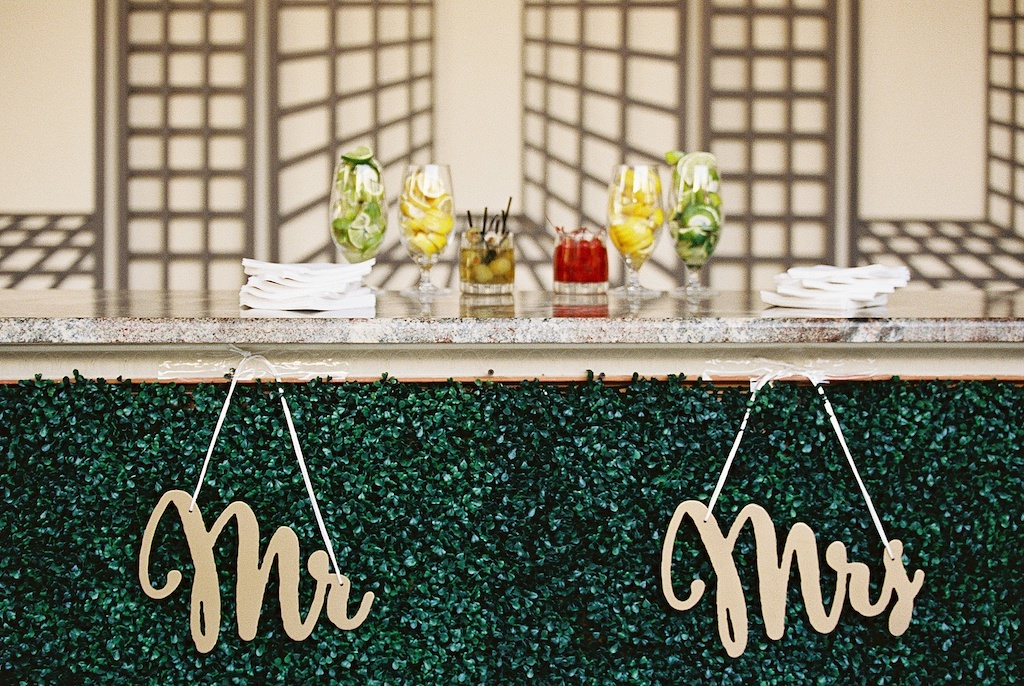 Garden Inspired Wedding Cocktail Hour Bar Decorated with Greenery Front and Gold Laser Cut Mr and Mrs Signs | Tampa Bay Wedding Florist Cotton & Magnolia