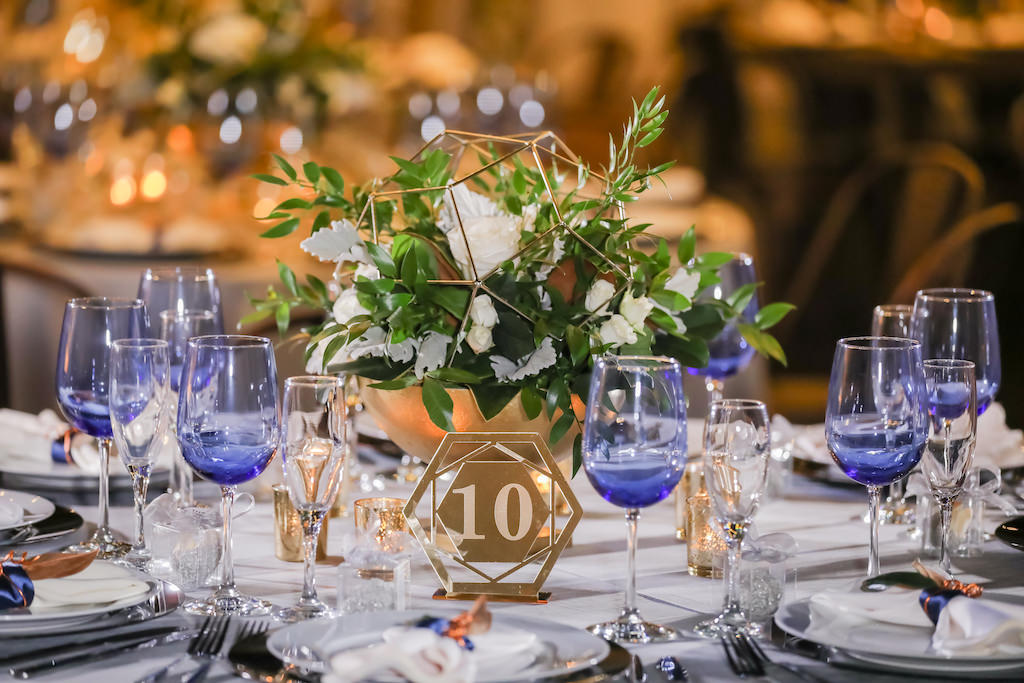 Industrial inspired Wedding Reception Decor, Gold Metal Geometric Shape with White and Greenery Florals, Gold Metal Geometric Table Number Sign, Blue Wine Glasses   Tampa Bay Wedding Photographer Lifelong Photography Studios