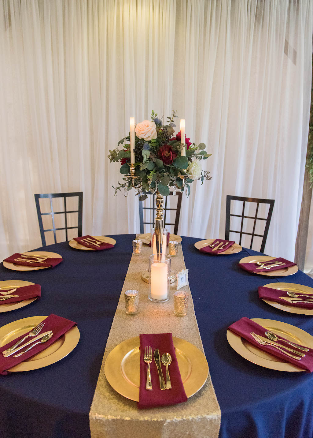 Rustic Wedding Reception Decor, Round Tables with Navy Blue Tablecloths, Gold Chargers and Burgundy Linens, Tall Silver Candlestick with Greenery, Ivory and Red Floral Bouquet Centerpiece, Gold Table Runner, Bistro Hanging Lights | Rustic Tampa Wedding Venue Kathleen's Garden