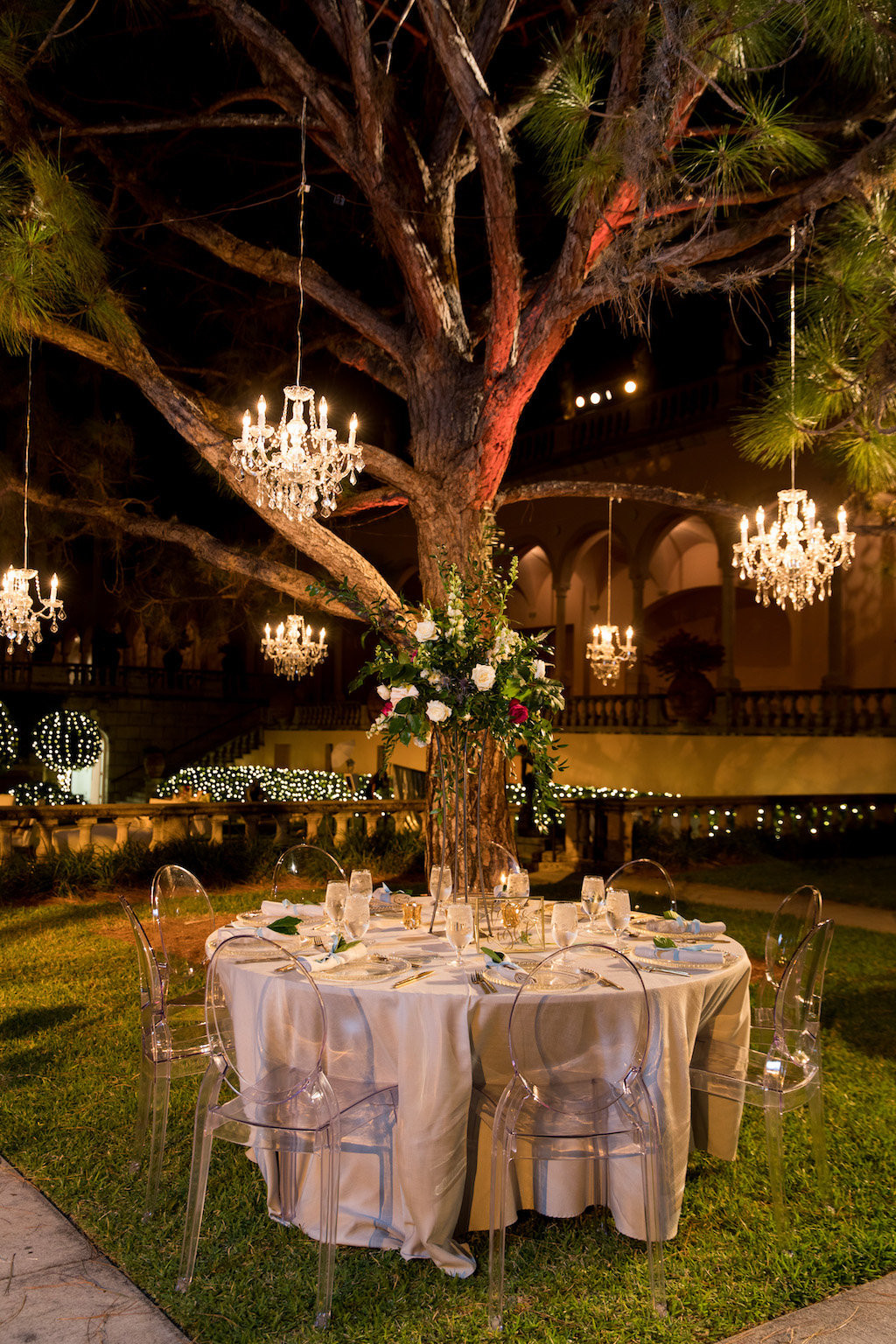 Nighttime Outdoor Garden Courtyard Wedding Reception Decor, Round Tables with Ivory Tablecloths, Ghost Chairs, Tall Greenery, White, Ivory, Red Floral Centerpiece, Crystal Chandeliers Hanging From Tree | Sarasota Wedding Venue Ringling Museum | Tampa Bay Wedding Planner NK Weddings