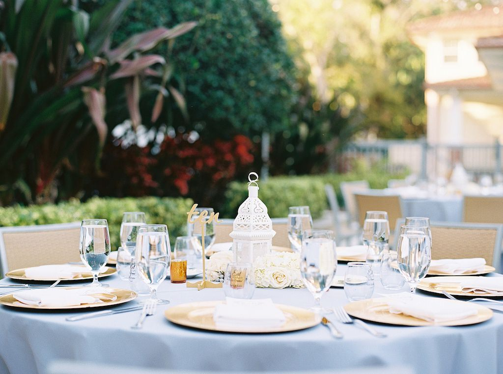 Garden Inspired Wedding Reception Decor, Round Tables with Dusty Blue Tablecloths, Gold Chargers, Small White Lantern Centerpieces and Ivory Garden Roses | Tampa Bay Wedding Florist Cotton & Magnolia