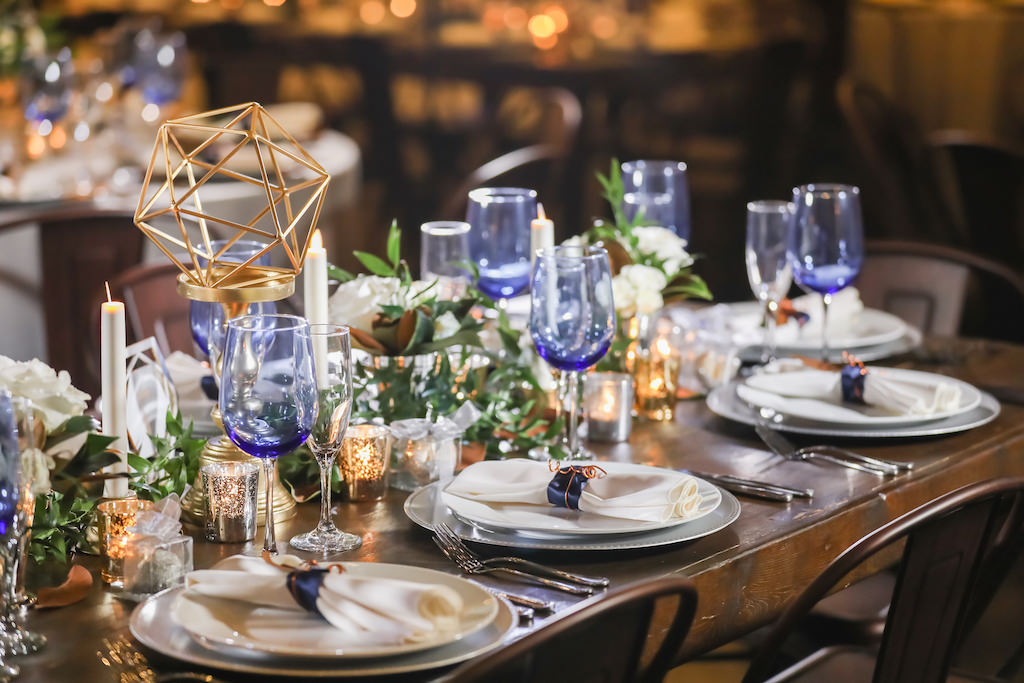Industrial Inspired Wedding Reception Decor, Long Brown Wooden Feasting Table with Greenery Garland, Gold Vase with Gold Geometric Shape Centerpiece, Candlesticks, Blue Wine Glasses, Silver Chargers and White Linens   Tampa Bay Wedding Photographer Lifelong Photography Studios