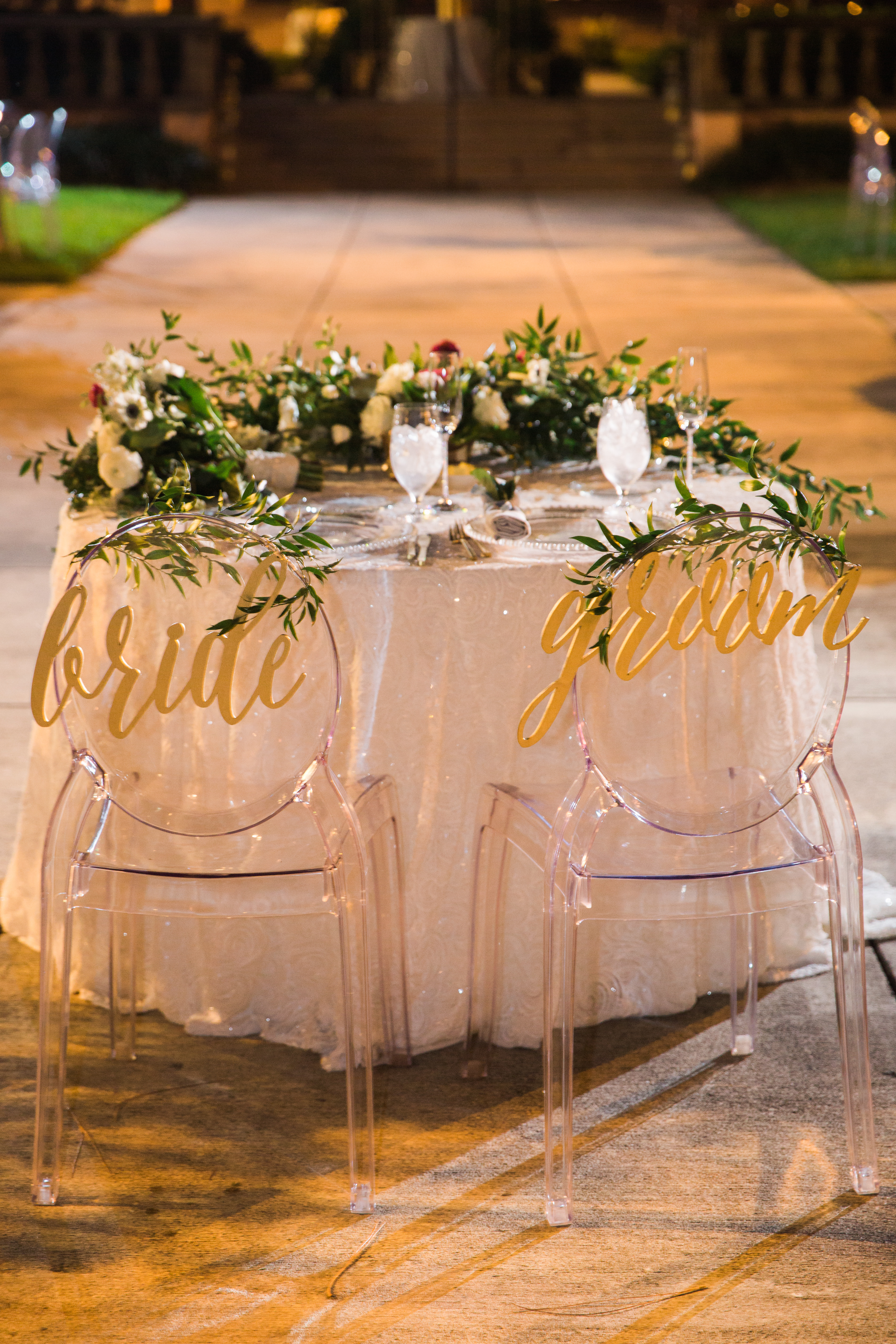 Outdoor Nighttime Garden Courtyard Wedding Reception Decor, Sweetheart Table with Ivory Tablecloth, Greenery Garland with White and Red Florals, Ghost Chairs with Laser Cut Bride and Groom Gold Signs | Tampa Bay Wedding Planner NK Weddings