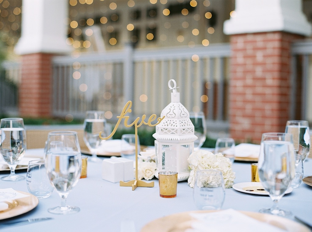 Garden Inspired Wedding Reception Decor, Round Tables with Dusty Blue Tablecloths, Gold Chargers, Small White Lantern Centerpieces, Gold Laser Cut Table Number Sign and Ivory Garden Roses | Tampa Bay Wedding Florist Cotton & Magnolia