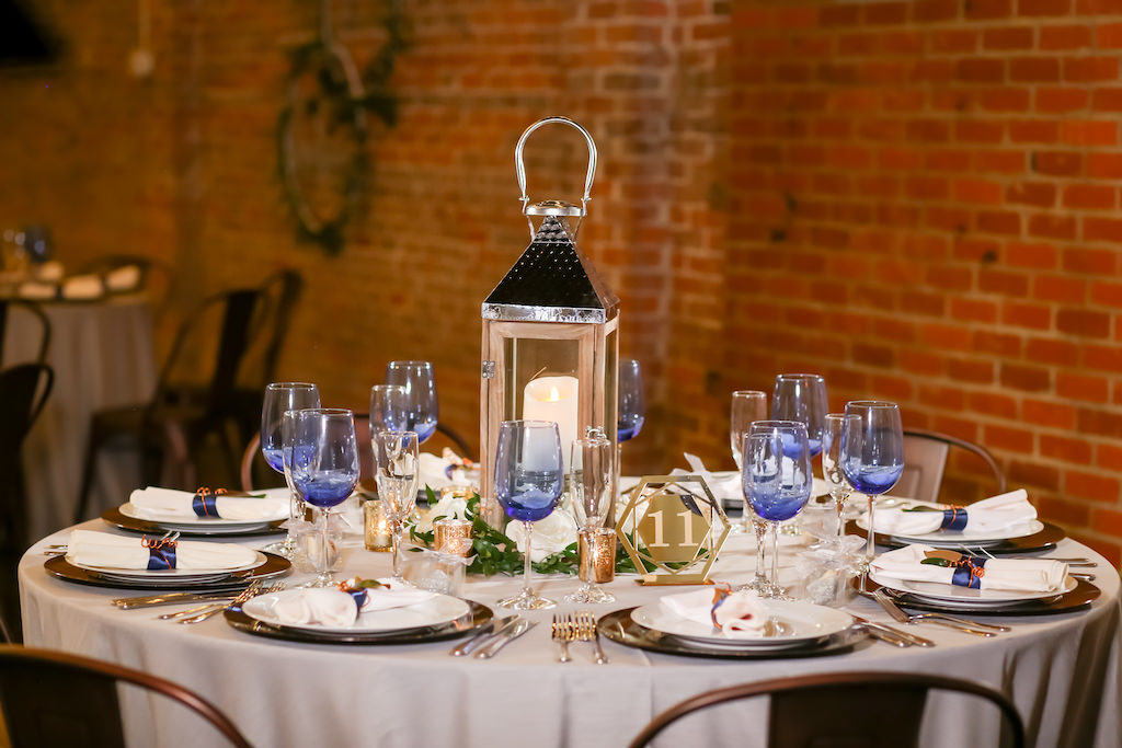 Industrial Inspired Wedding Reception Decor, Round Table with Grey Tablecloth, Blue Wine Glasses, Silver Lantern with Candle, Gold Geometric Metal Table Number Tampa Bay Wedding Photographer Lifelong Photography Studios