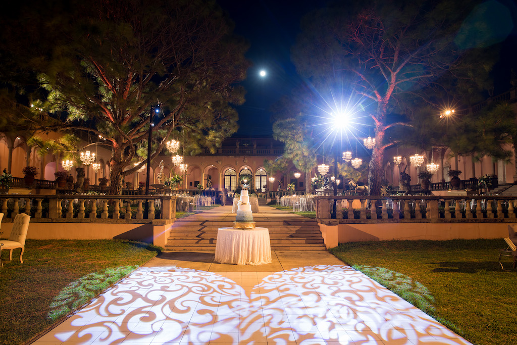 Nighttime Outdoor Garden Courtyard Wedding Reception Decor, Heart Shaped Projection, Round Table with Five Tier Wedding Cake on Gold Stand | Sarasota Wedding Venue Ringling Museum | Tampa Bay Wedding Planner NK Weddings