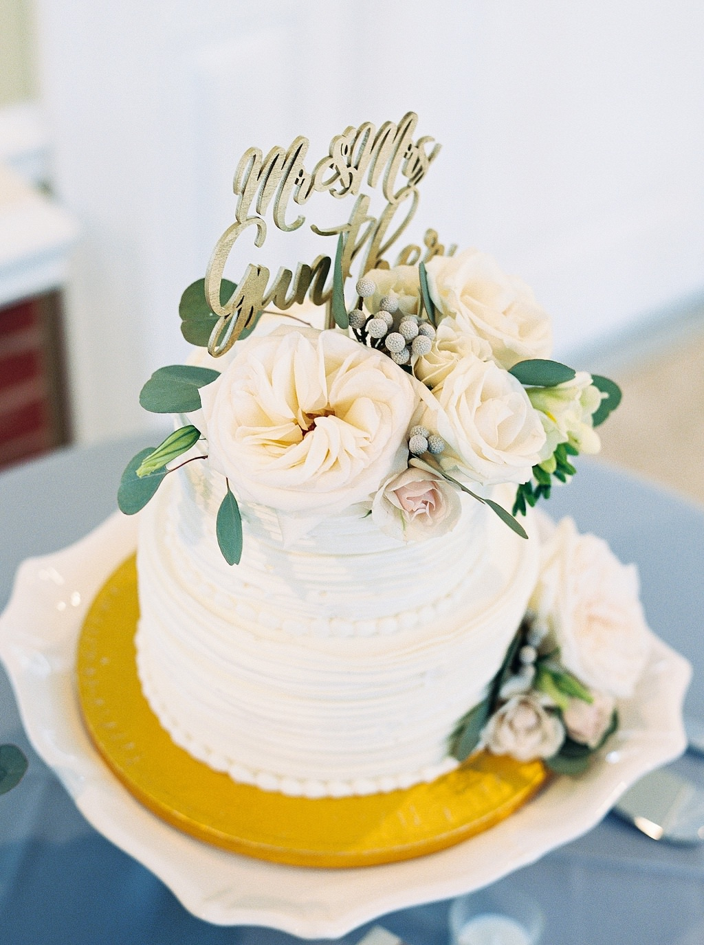 Two Tier White Ruffle and Beaded Wedding Cake with Real Ivory Garden Roses and Silver Dollar Eucalyptus Cake Topper and Gold Laser Cut Custom Cake Topper | Tampa Bay Wedding Florist Cotton & Magnolia