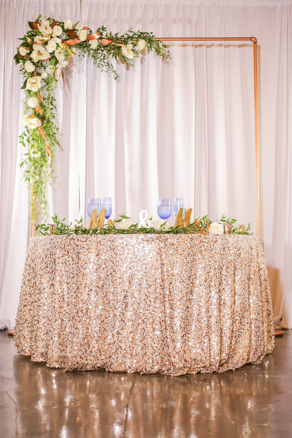 Industrial Inspired Wedding Reception Decor, Gold Metal Arch with White and Greenery Florals, Sweetheart Table with Sparkle Blush Pink Tablecloth, Gold Mr and Mrs Sign and Greenery Garland   Tampa Bay Wedding Photographer Lifelong Photography Studios