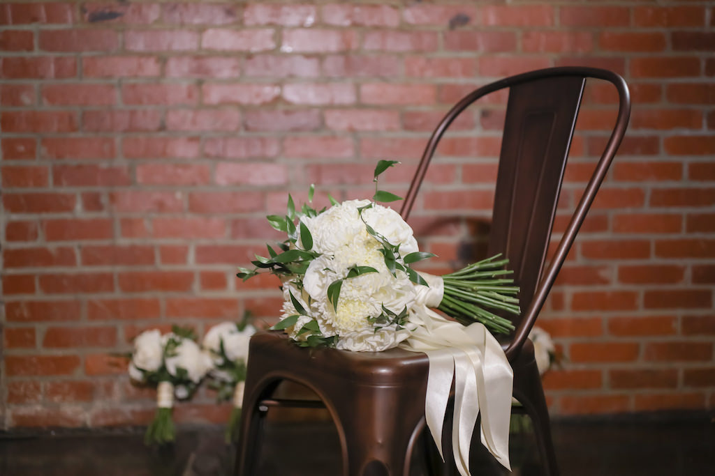 Industrial Inspired Wedding, White and Greenery Floral Bouquet on Bronze Metal Chair   Tampa Bay Wedding Photographer Lifelong Photography Studios   Tampa Unique Industrial Wedding Venue CAVU
