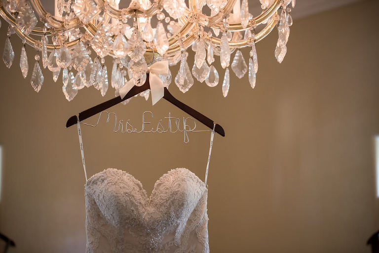 Sweetheart Stella York Strapless Lace and Rhinestone Embellished Wedding Dress on Personalized Wire and Wooden Hanger Hanging on Chandelier | Sarasota Wedding Photographer Cat Pennenga Photography