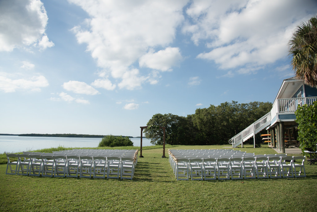 Outdoor Florida Wedding Ceremony Decor, White Wooden Folding Chairs, Wooden Ceremony Arch | St. Pete Waterfront Wedding Venue Tampa Bay Watch